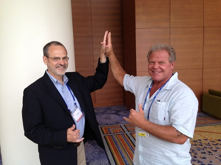 Catholic speaker Gary Zimak giving a high five to his friend and fellow evangelist Bear Woznick